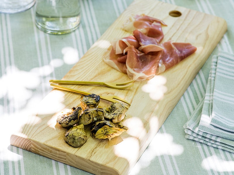 Charcuterie on a wooden meze board on a sun-dappled table