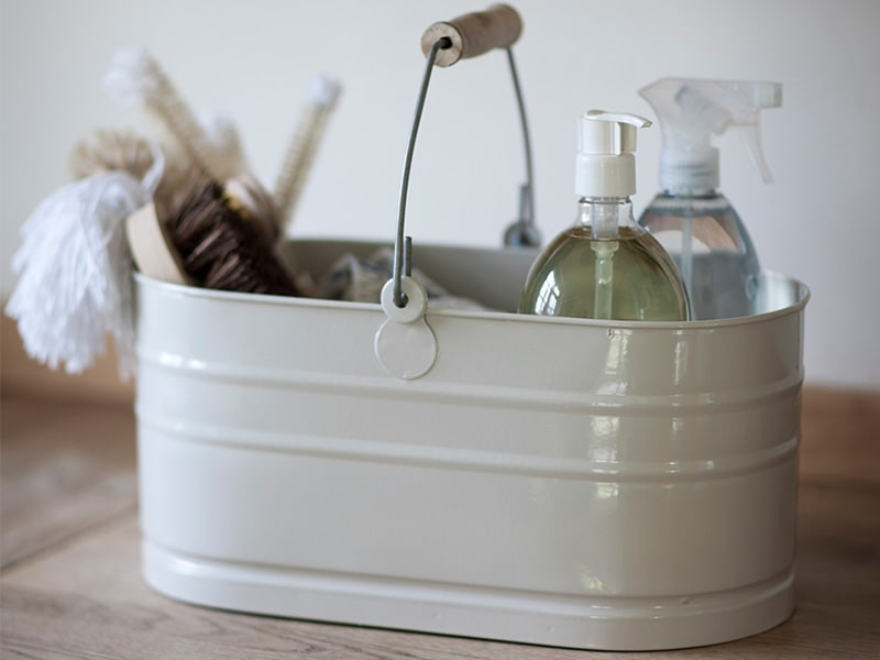 Cleaning products in a chalk coloured tidy with a wooden handle