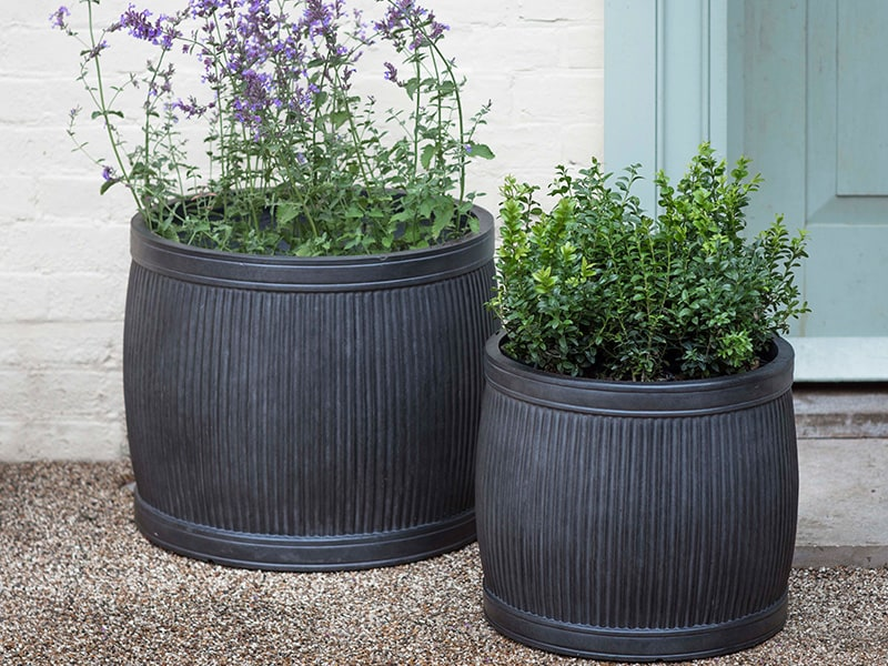 Round Bathford planters set against cream brick garden wall