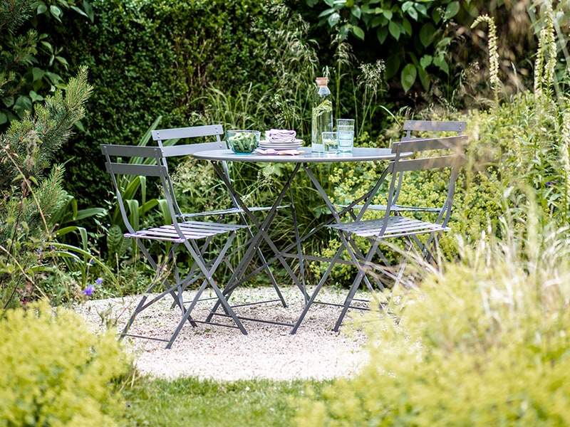 Large bistro set in garden laid with drinks and snacks