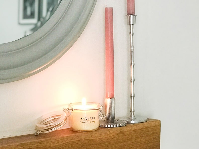 Sea salt candle with two candlesticks on a mantelpiece next to mirror