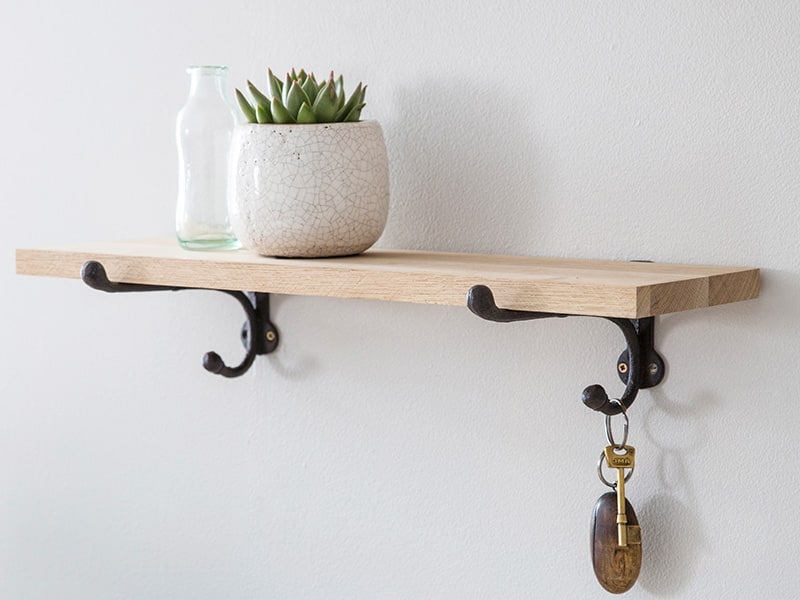 Pale Wood shelf on cast iron brackets with small plant and bottle vase