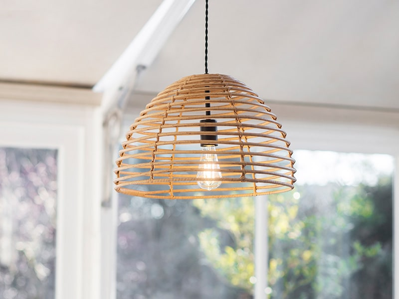 Woven PE Bamboo pendant light hanging in bright, airy conservatory