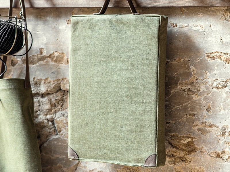 Green garden kneeler hanging on wooden peg rail