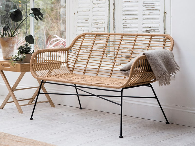 All-weather bamboo bench in conservatory with white washed shutters and floor