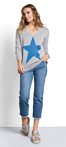 Model wears our signature star v neck jumper in a lightweight knit in grey marl and french blue star