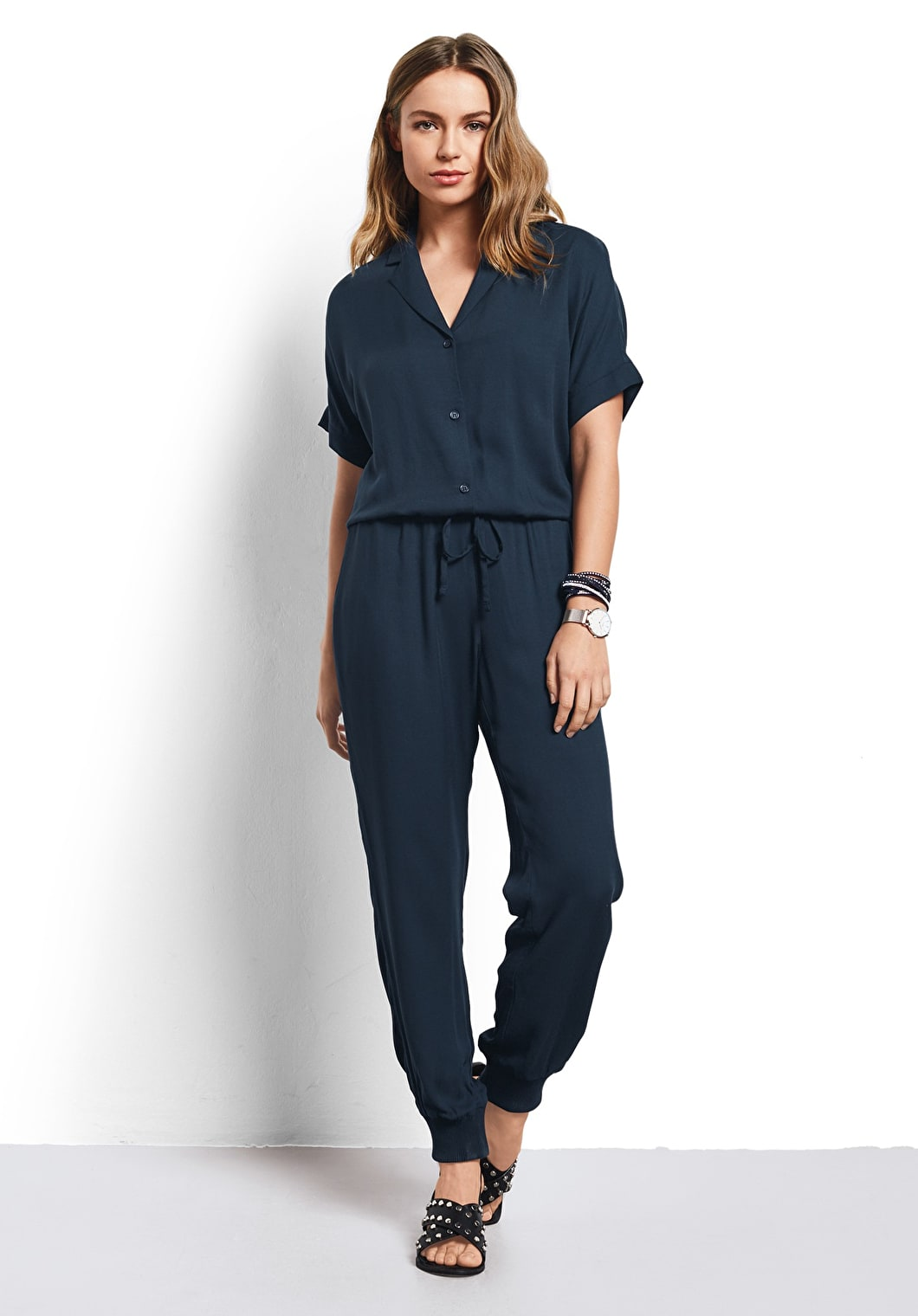 Model wears our lightweight jumpsuit with a waist cinching tie and button up shirt in Blueberry