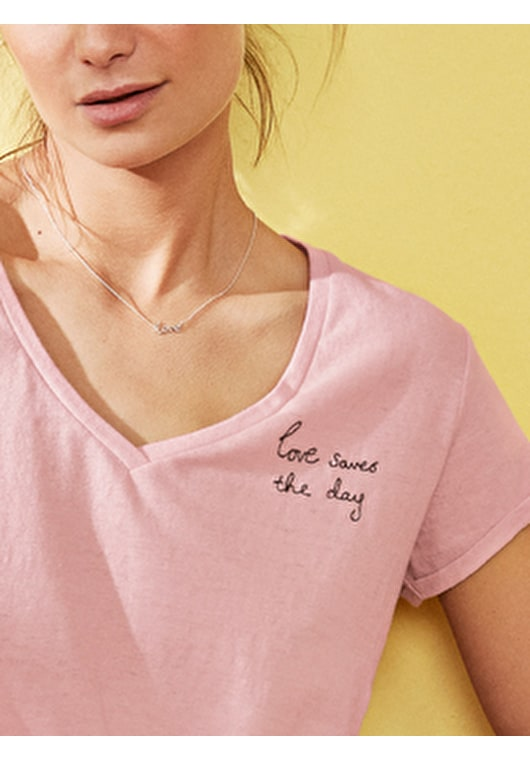 Model wears our Love Saves the Day' embroidered v neck t shirt in coral blush and black