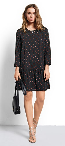 Model wears a relaxed drop waist sunstar print dress in black and picante with 3/4 length sleeves