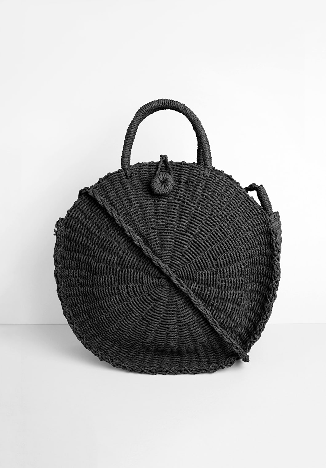 black round woven bag with a crossbody strap and handles with knot and loop fastening