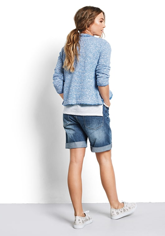 Woman wearing our soft knitted jacket with frayed edge detailing in a stunning french blue and white