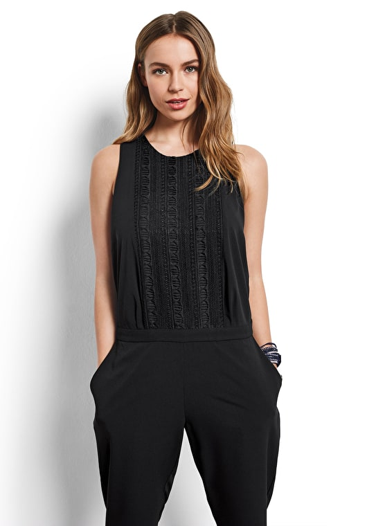 Model wears our black jumpsuit with lace detailing at the front of the top