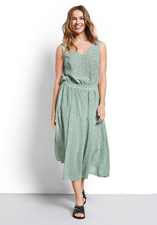Model wears our stunning ditsy granite green dress combines our flowing midi skirt with a relaxed top with a semi sheer hem
