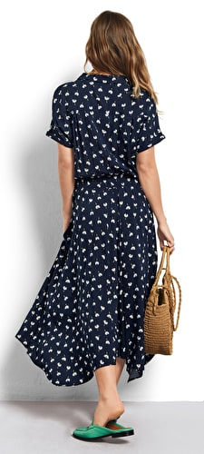 Model wears our shirt dress with a nipped in waist and asymmetric hem with a stunning daisy print in a midnight blue