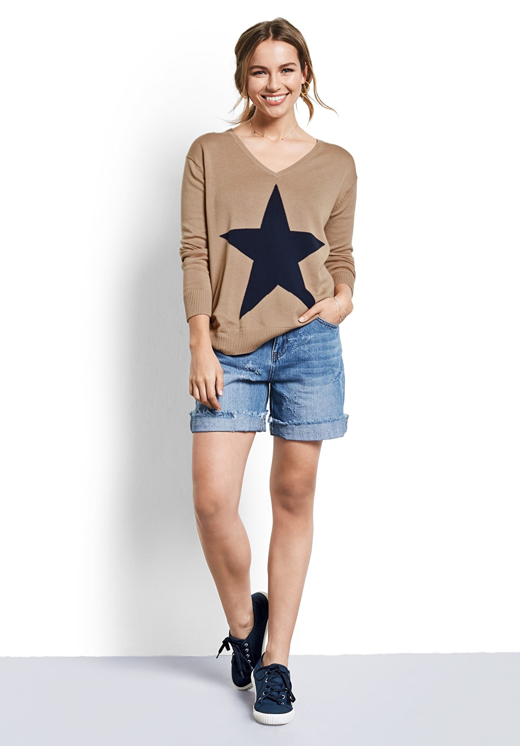 Model wears our signature star v neck jumper in a lightweight knit in Camel and midnight star