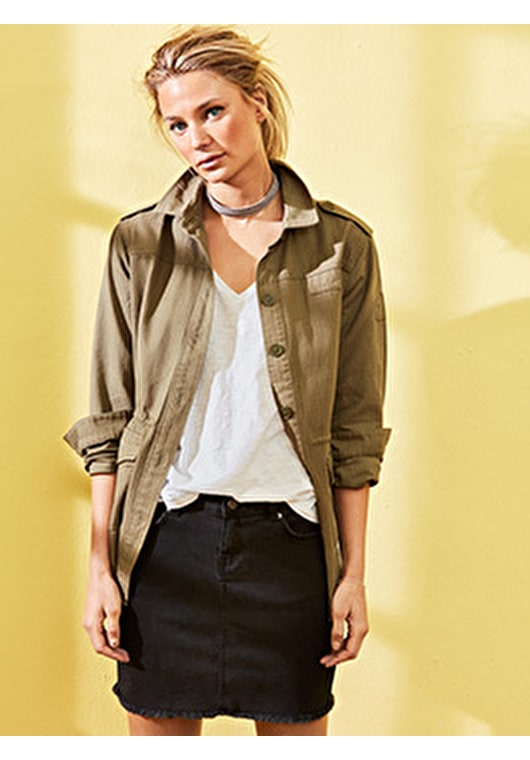 Model wears our long length embroidered khaki military jacket with a gold diamond embroidered on the back