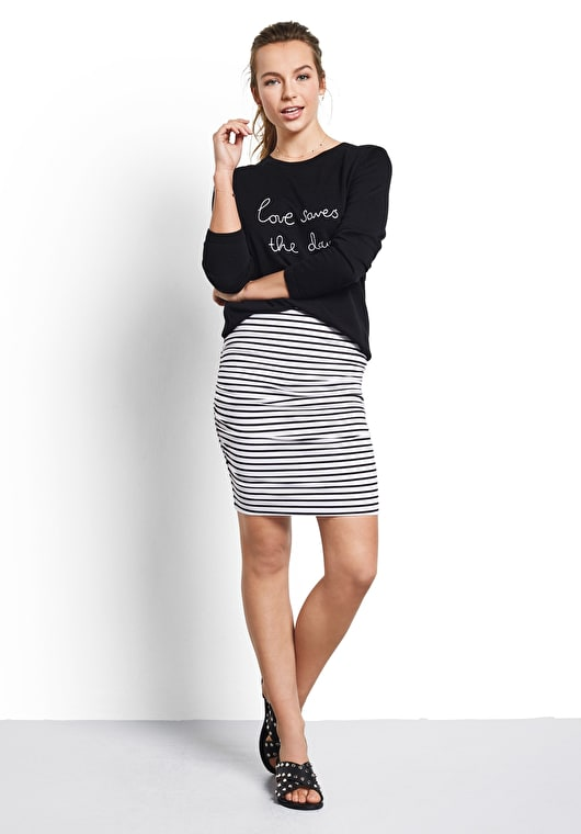 Model wears our form fitting ruched skirt in white and black stripes