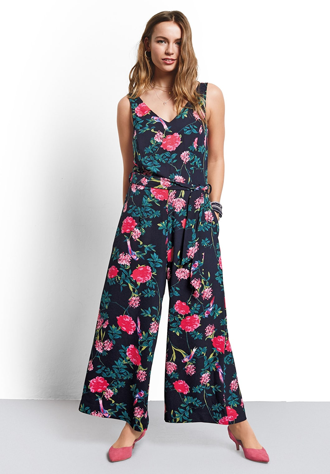Model wears our jumpsuit with a detachable belt, wide leg trousers and a v neckline in an ornate midnight print