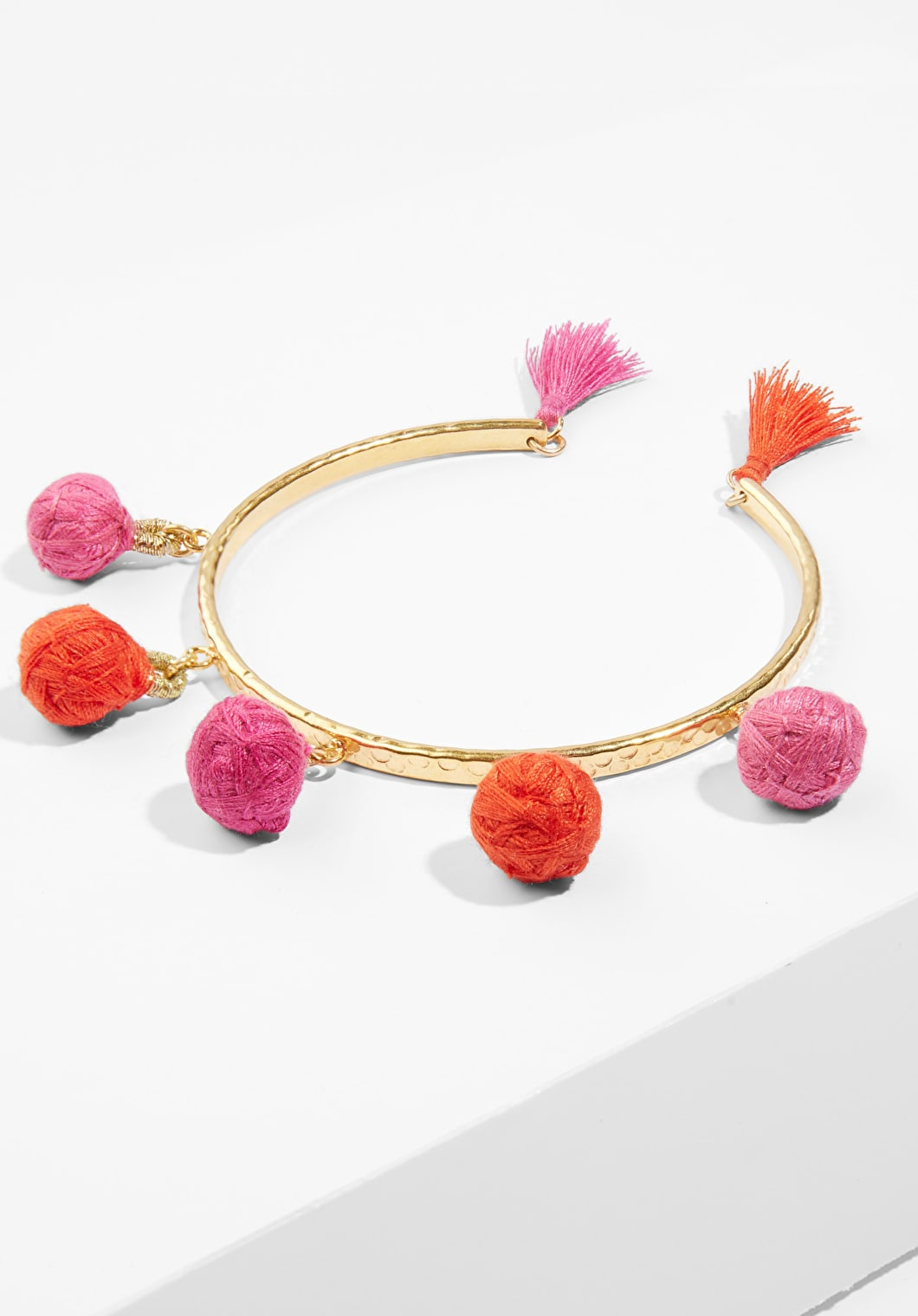 Multi coloured pink pom pom bangle with a gold band