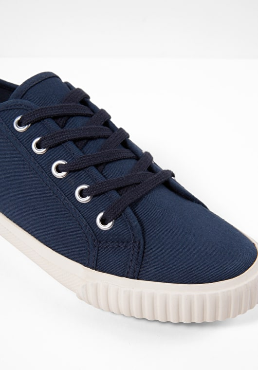 Navy Canvas Trainers which include metal eyelets, woven laces and ribbed rubber soles.
