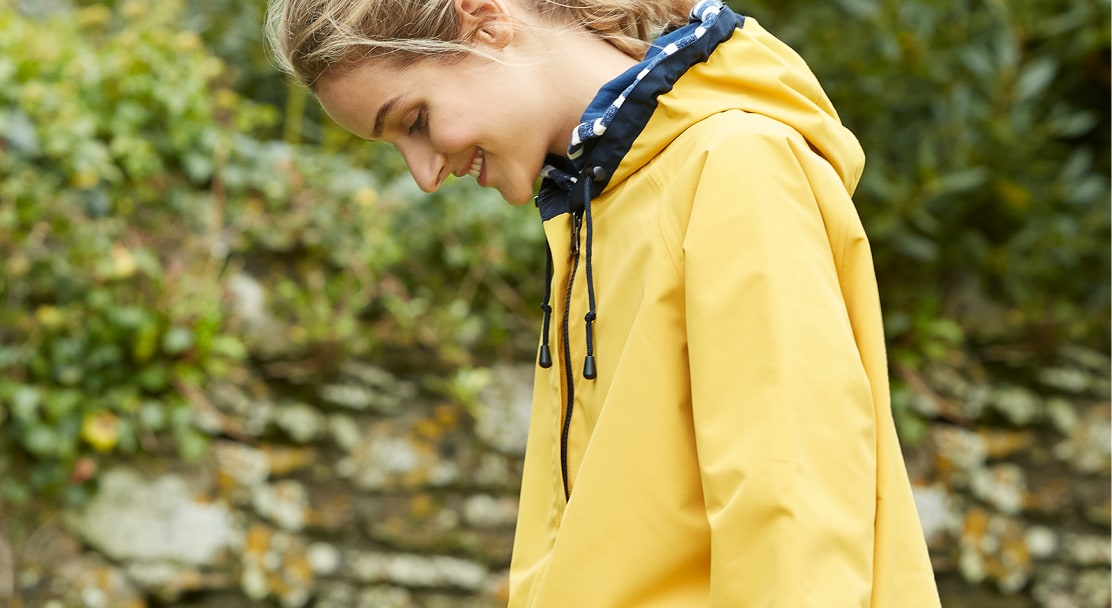 Close up of Lady wearing the Reversible Raincoat in yellow.