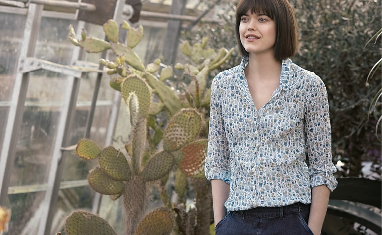 Dark haired lady standing infront of cacti wearing the Larissa Shirt