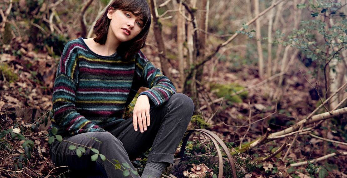 Lady with a stripey kitted jumper forgaging for mushrooms in the woods.