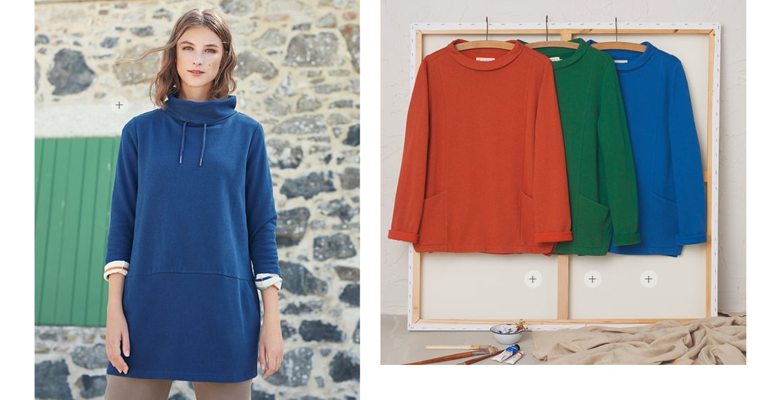 Women wearing oversized blue pullover jumper, Other colourful versions of the same top on hangers next to her.