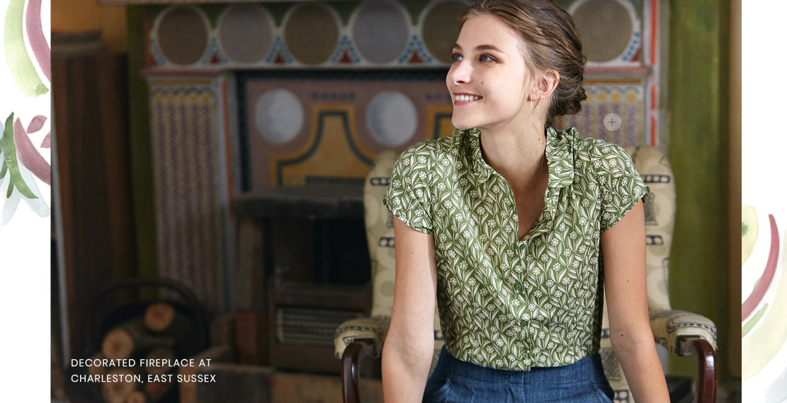 A woman posing in front of the fireplace. Wearing a light green top with a flowery pattern.