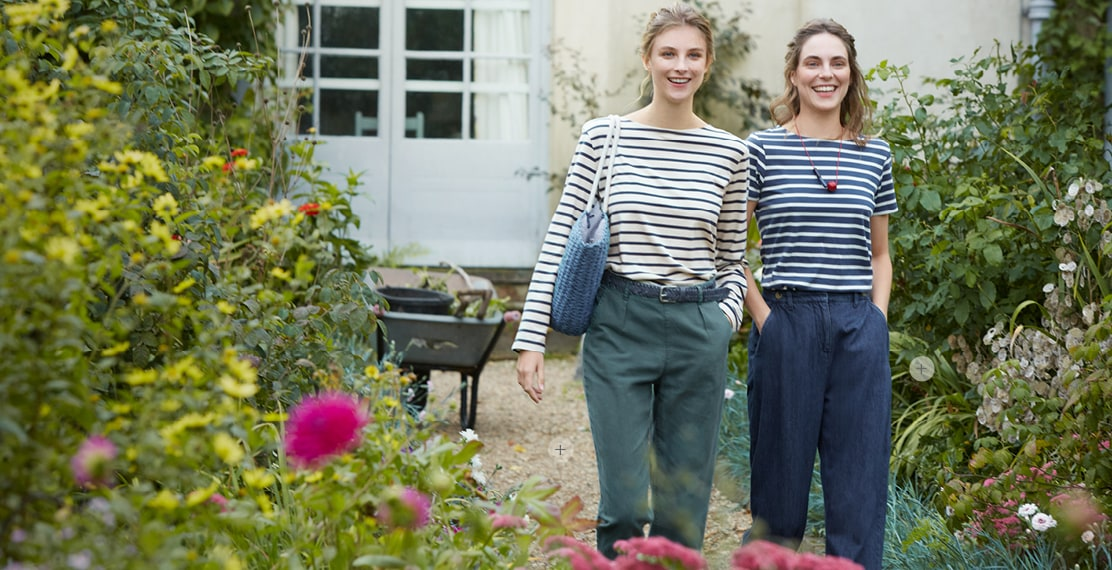 2 girls wearing classic breton striped tops, one with a blue canvas handbag and green trousers. The other, wearing jeans and a red necklace. In the garden of Charleston House.